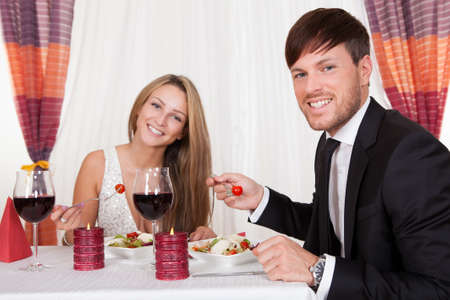 Young couple seated at a restaurant table enjoying a romantic dinner by candlelight and drinking red wine Stock Photo - 16522228