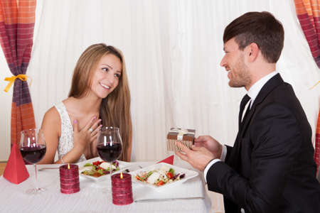 'evening wear': Happy young woman receives a gift from her partner. Romantic dinner setting with young couple dressed in evening wear