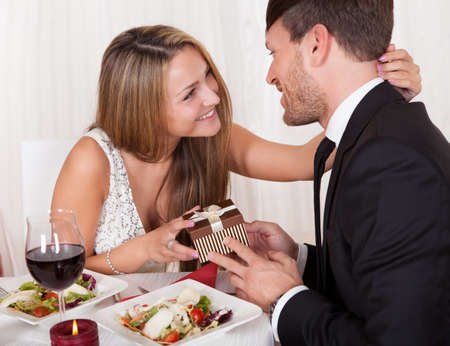 'evening wear': Happy young woman gives a gift to her partner. Romantic dinner setting with young couple dressed in evening wear