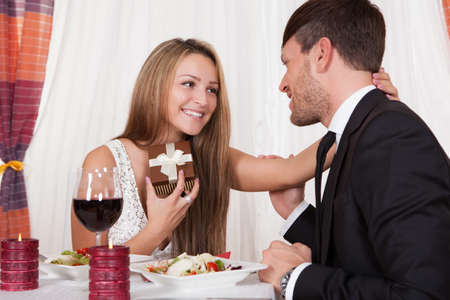 Happy young woman receives a gift from her partner. Romantic dinner setting with young couple dressed in evening wear photo