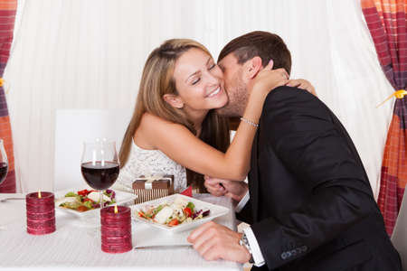 dinner wear: Happy young woman receives a gift from her partner. Romantic dinner setting with young couple dressed in evening wear
