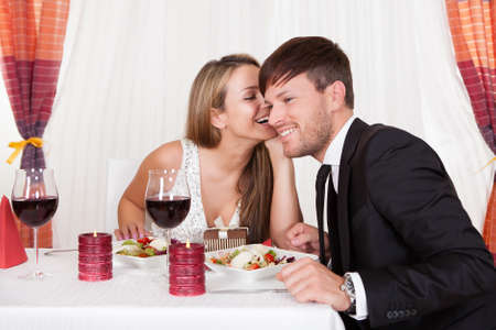 Romantic lovers sitting at an elegant restaurant table enjoying a meal and sharing secrets whispering to each other Stock Photo - 16522398