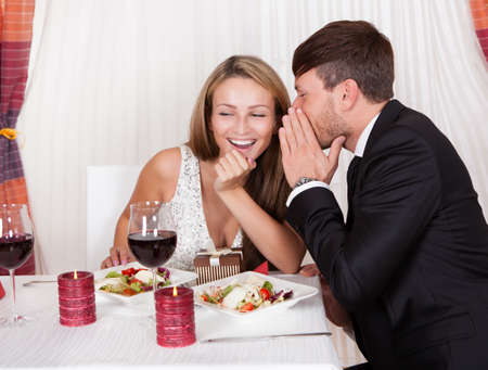 Romantic lovers sitting at an elegant restaurant table enjoying a meal and sharing secrets whispering to each other Stock Photo - 16522137
