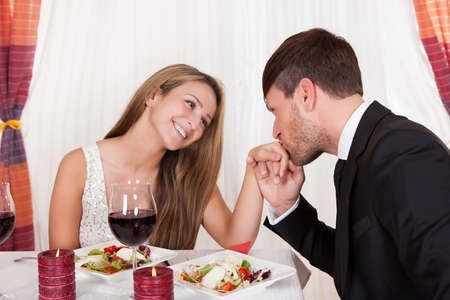 dating couples: Man kissing a womans hand at a romantic dinner as she looks at him with an adoring expression and lovely smile Stock Photo