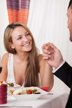 Man holding a womans hand at a romantic dinner as she looks at him with an adoring expression and lovely smile photo