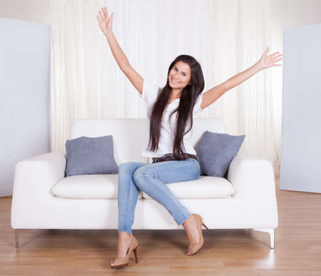 sexy housewife: Beautiful stylish young woman sitting on a couch in her living room with her arms thrown wide open smiling happily