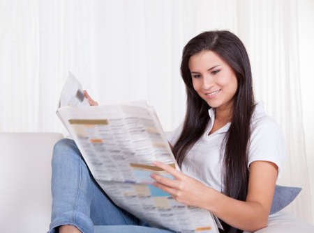 reading news: Attractive young woman sitting relaxing on a couch reading a newspaper with a cheerful smile