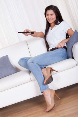 Smiling woman sitting on a couch with a remote control in her hands with copyspace over white curtains Stock Photo - 16522399