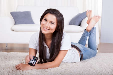 Smiling woman sitting on a couch with a remote control in her hands with copyspace over white curtains Stock Photo - 16522154
