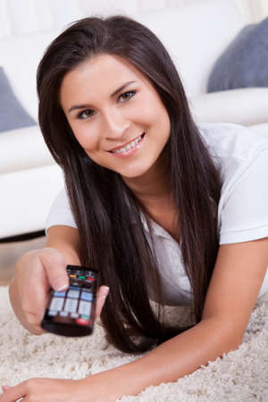 Smiling woman sitting on a couch with a remote control in her hands with copyspace over white curtains Stock Photo - 16522201