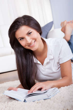 Attractive casual young woman lying on her stomach on a carpet in her living room reading a book photo