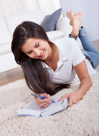Attractive casual young woman lying on the carpet in her living room writing in a diary or journal photo