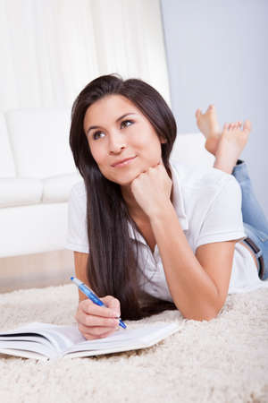 Beautiful woman daydreaming as she lies on the floor writing in her diary or journal Stock Photo - 16522139