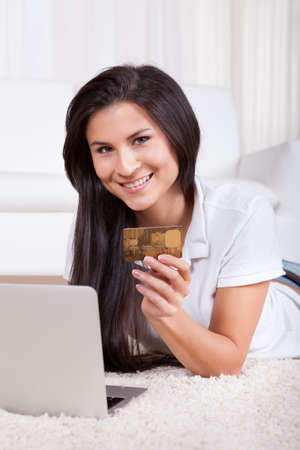 Woman shopping online holding her credit card in her hand as she enters the details in payment for her purchase photo