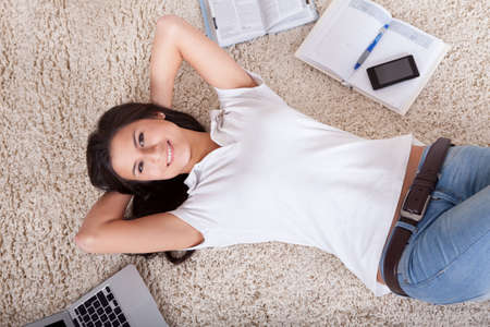 lying on back: Overhead view of a young woman lying on her back on a carpet alongside her laptop daydreaming