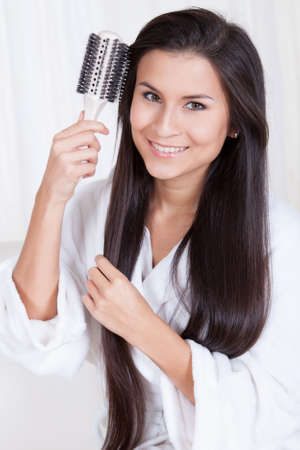 combing hair: Beautiful woman sitting in a fresh white robe brushing her long straight brunette hair