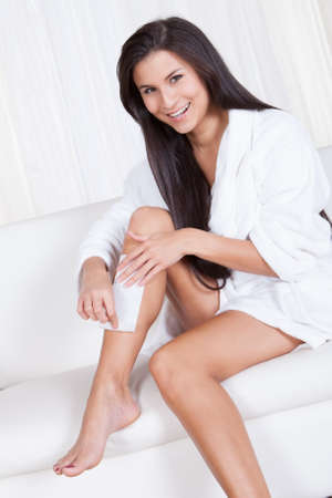 Beautiful woman sitting on a couch in a white toweling robe waxing her legs with hot wax and a fabric strip photo