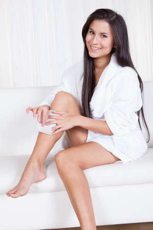 Beautiful woman sitting on a couch in a white toweling robe waxing her legs with hot wax and a fabric strip Stock Photo - 16522540