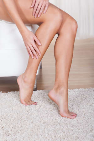 Cropped view image of a young woman stroking her shapely legs with her hands after waxing them photo