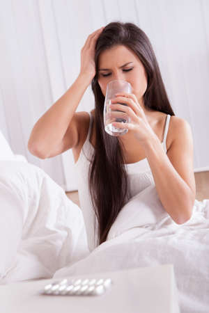 Ill woman in bed taking medication sitting up holding a glass of water looking at a tablet in her hand photo