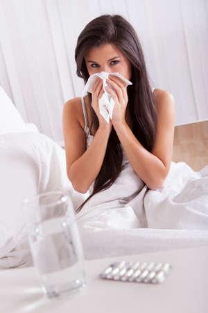 estornudo: Mujer enferma en cama con un resfriado y la gripe estacional