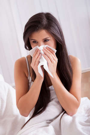 Woman ill in bed with a seasonal cold and flu photo