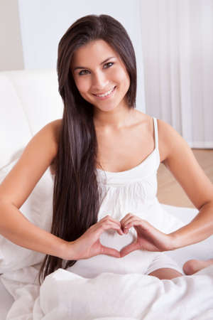 Beautiful smiling pregnant woman sitting on a bed making a heart sign with her fingers over her swollen belly photo