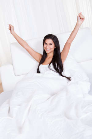 refreshed: Refreshed young woman rejoicing in bed with her arms outstretched above her head rejuvenated by a good nights sleep