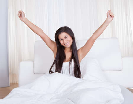 Refreshed young woman rejoicing in bed with her arms outstretched above her head rejuvenated by a good nights sleep