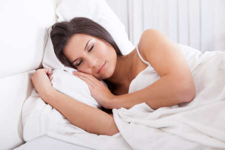 Closeup portrait of a beautiful young woman sleeping peacefully in her bed facing the camera photo