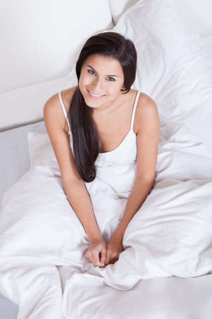 Pretty young woman snuggling down in bed as she smiles up at the camera Stock Photo - 16522636