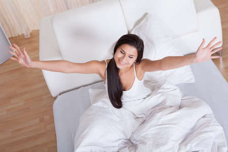 waking: Pretty young woman snuggling down in bed as she smiles up at the camera