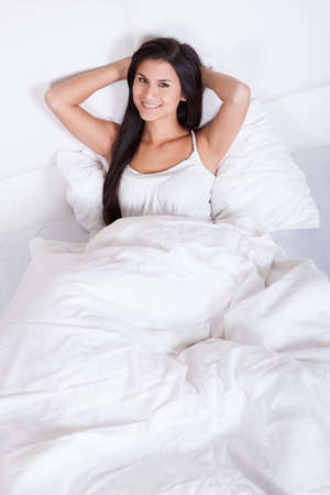 snuggling: Pretty young woman snuggling down in bed as she smiles up at the camera