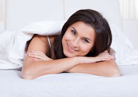 Smiling woman lying on her stomach on her bed under the bedclothes Stock Photo - 16522565