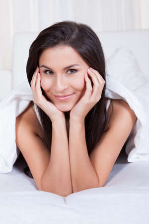 Smiling woman lying on her stomach on her bed under the bedclothes resting her chin on her hands Stock Photo - 16522553