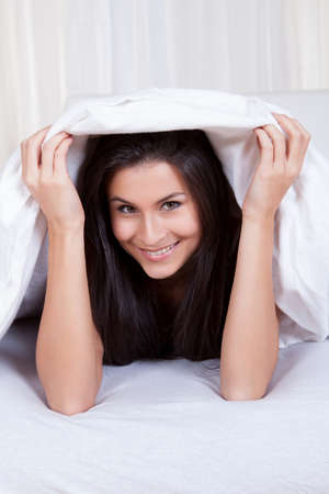 Smiling woman lying on her stomach on her bed under the bedclothes Stock Photo - 16522574