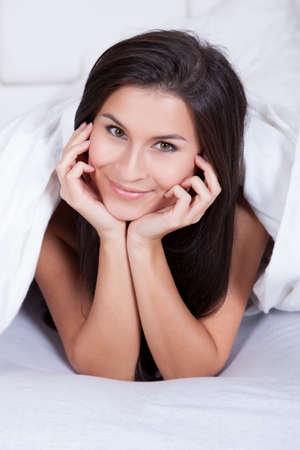 Smiling woman lying on her stomach on her bed under the bedclothes resting her chin on her hands Stock Photo - 16522062