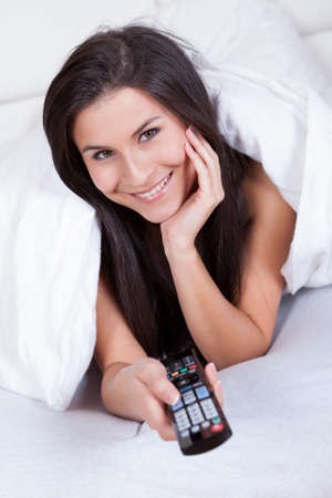 Woman lying in bed under the bedclothes with a remote control in her hand smiling happily Stock Photo - 16522323