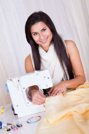 Smiling young woman or seamstress working with her sewing machine stitching a long length of fabric Stock Photo - 16522191