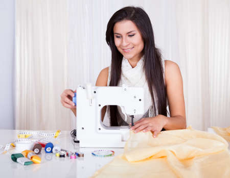 Smiling young woman or seamstress working with her sewing machine stitching a long length of fabric Stock Photo - 16522284