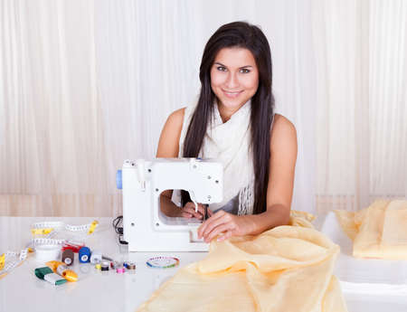 Smiling young woman or seamstress working with her sewing machine stitching a long length of fabric photo