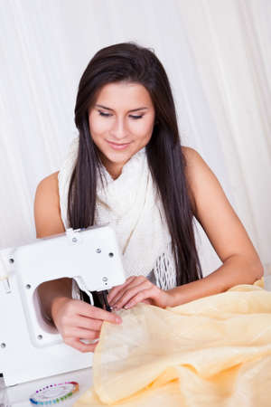 Smiling young woman or seamstress working with her sewing machine stitching a long length of fabric Stock Photo - 16522220