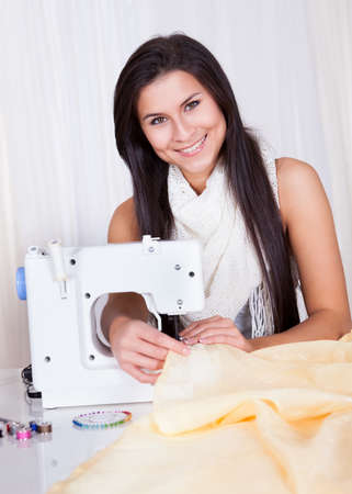 Smiling young woman or seamstress working with her sewing machine stitching a long length of fabric Stock Photo - 16522598