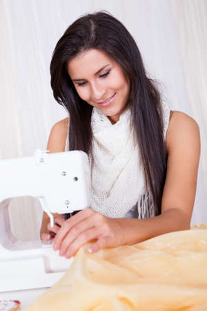 tilted view: Smiling young woman or seamstress working with her sewing machine stitching a long length of fabric