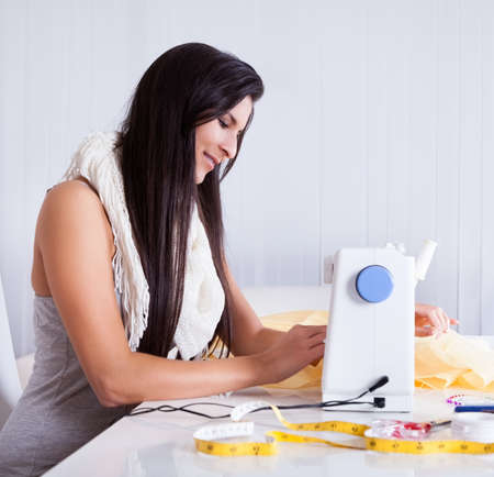 Smiling young woman or seamstress working with her sewing machine stitching a long length of fabric Stock Photo - 16522629