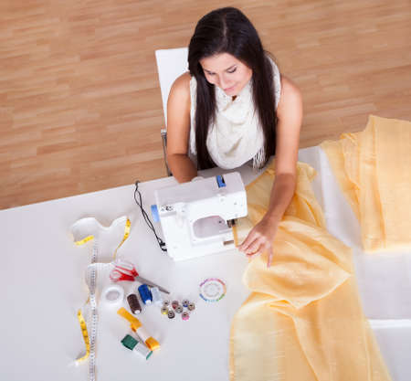 stitching machine: Smiling young woman or seamstress working with her sewing machine stitching a long length of fabric