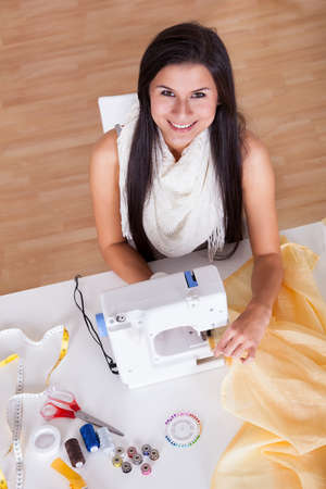 Smiling young woman or seamstress working with her sewing machine stitching a long length of fabric Stock Photo - 16522554