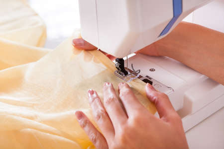 stitching machine: Close-up on woman working with her sewing machine stitching a long length of fabric