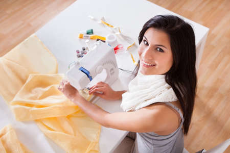 Smiling young woman or seamstress working with her sewing machine stitching a long length of fabric Stock Photo - 16522279
