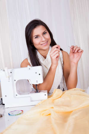 threading: Smiling beautiful woman seated at a table with a length of fabric holding a reel of cotton threading her sewing machine